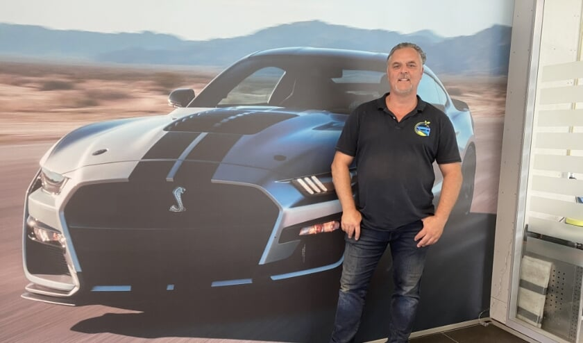 Ronald ten Kleij voor de wandgrote poster van een van zijn favoriete auto's, een Mustang Shelby (foto: Karin van der Velden)