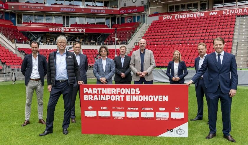 Alle bestuursleden bij elkaar op het gras van het PSV-stadion.