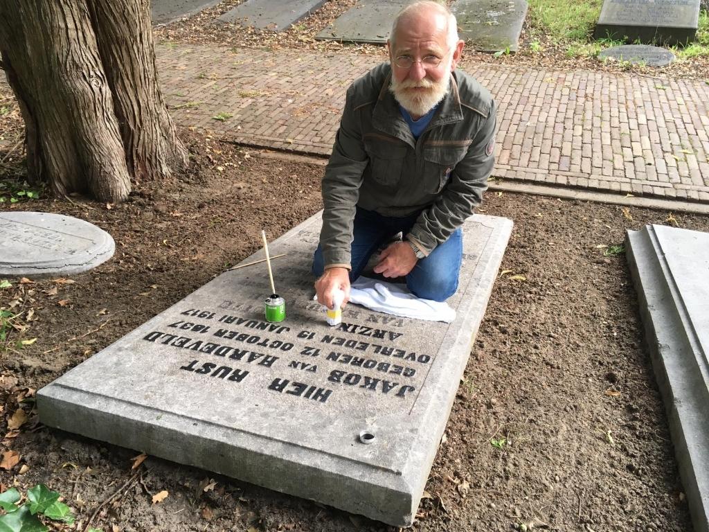 Hans Weijers is één van de actieve Vrienden van het Gedenkpark de Oude Begraafplaats. Maandag was hij bezig om de teksten op de grafstenen beter naar voren te halen. Foto:  © DPG Media