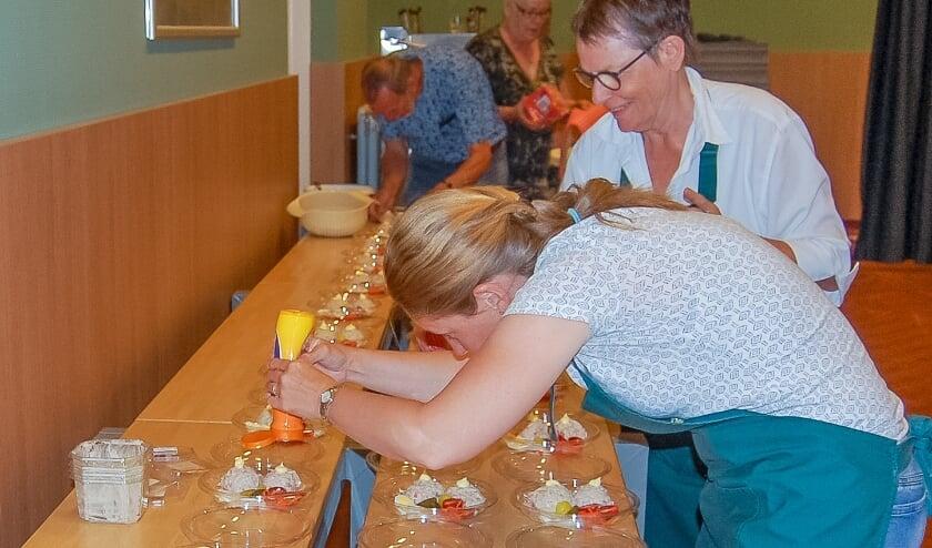 Het team van Samen Eten aan de slag voor de verrassingsmaaltijd voor de ouderen in Babberich. (foto: Willy Kuijpers)