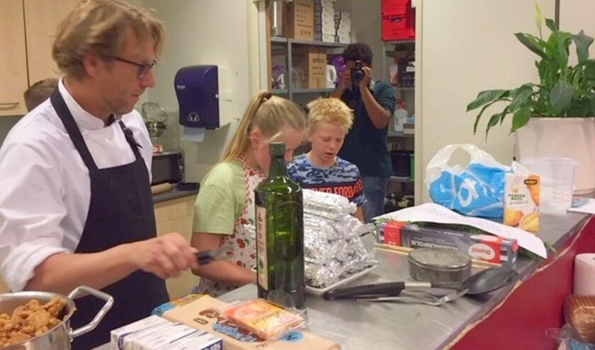 Twee leerlingen zijn onder begeleiding druk bezig in de keuken met het diner, terwijl ander leerlingen de zaal inrichten, tafels dekken en andere voorbereidingen treffen. (Foto: De Trekvogel)