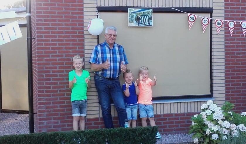 Aart met zijn trotse kleinzoons voor zijn versierde huis.
