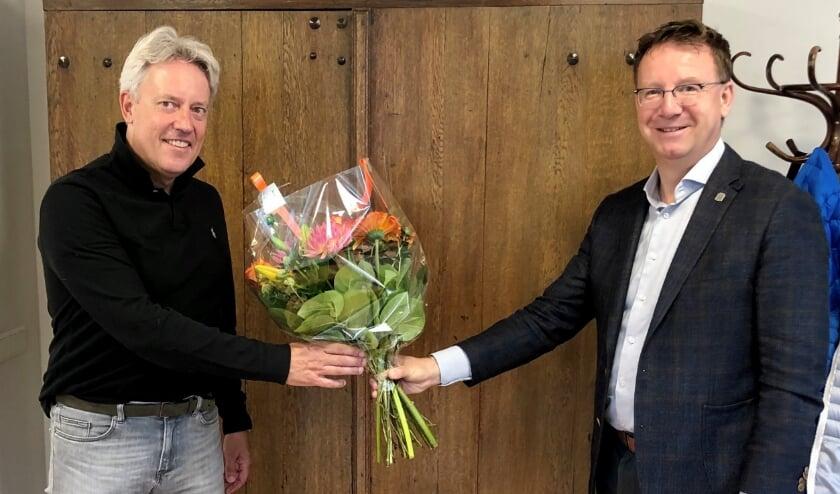 Burgemeester Patrick Van Domburg bedankt Richard Brugel voor zijn succesvolle Burgernetactie met een mooie bos bloemen. (Foto: gemeente IJsselstein)