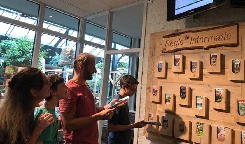 Bezoekers raadplegen de monitor bij Landal Miggelenberg..