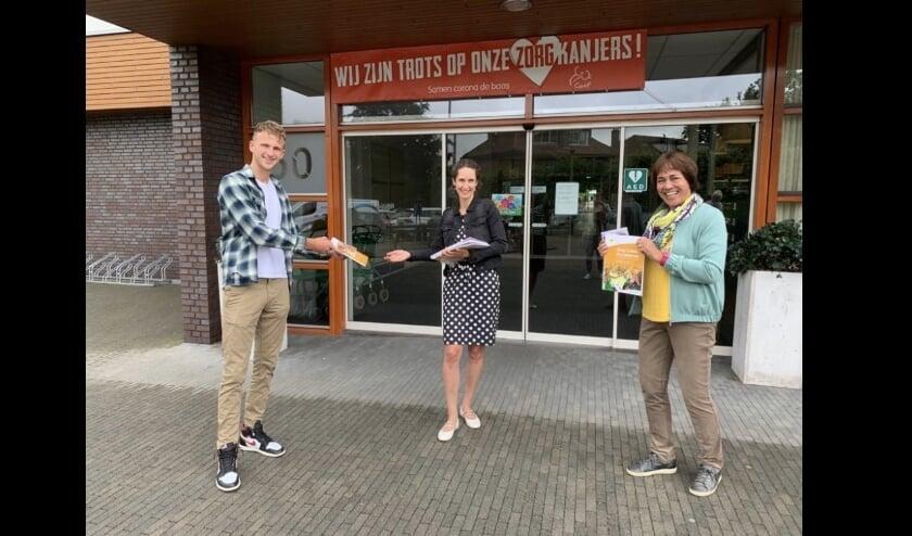 Max de la Fuente (links) en Patsy Heida (rechts) overhandigen de Zing-Cirkel boeken aan Corrine Korevaar