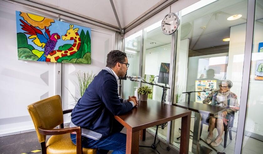 Wethouder Marc Wilson voert een raamgesprek met een bewoner van verzorgingshuis Rozenburght. (Foto: Frank de Roo)
