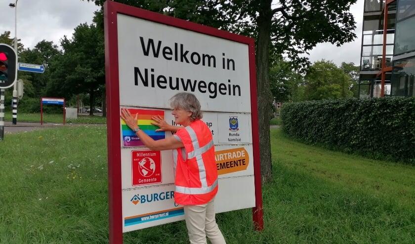 Wethouder Marieke Schouten plakt de vermelding van de vriendschap tussen Nieuwegein en Pulawy op een toegangsbord symbolisch af met een regenboogsticker. Eigen foto