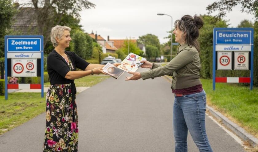 Mediator Pauline Houweling en illustrator Suzanne Huijs wisselen hun nieuwe boeken uit op de dorpsgrens
