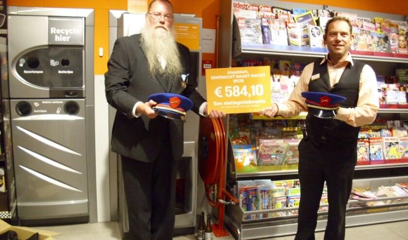 bestuurslid F Sluijs krijgt de cheque van filiaalmanager J Kremer