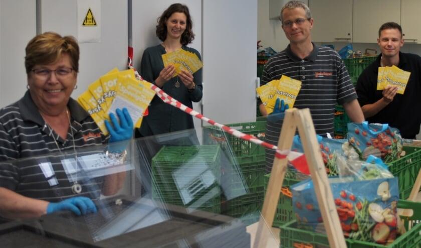 Vrijwilligers van Voedselbank Scheveningen  nemen de speelngoedbonnen in ontvangst.