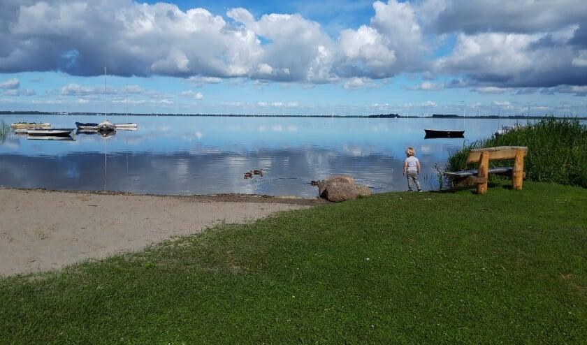 Kleine kleuter geniet van het water en het zand op het Schipperstrand.