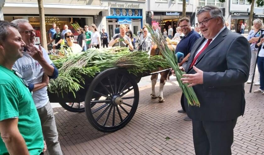 Burgemeester Bruls met een bos gladiolen.