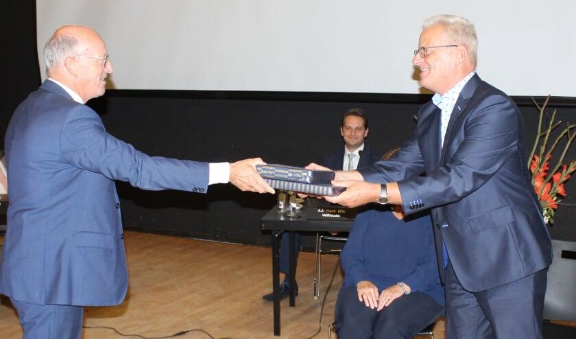 De heer Platschorre, vicevoorzitter van de gemeenteraad, overhandigt een afscheidscadeau overhandigt aan Jaap Visser. (Foto: pr)