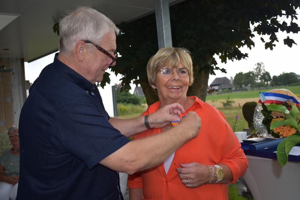 Herma Mennegat krijgt het lintje opgespeld door haar man Henk.   © DPG Media