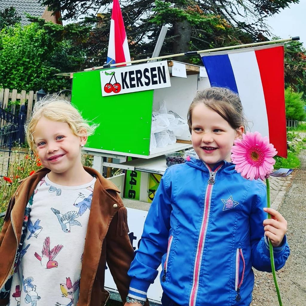 kinderen brengen bloemen rond Foto: Claudia van Trigt © DPG Media