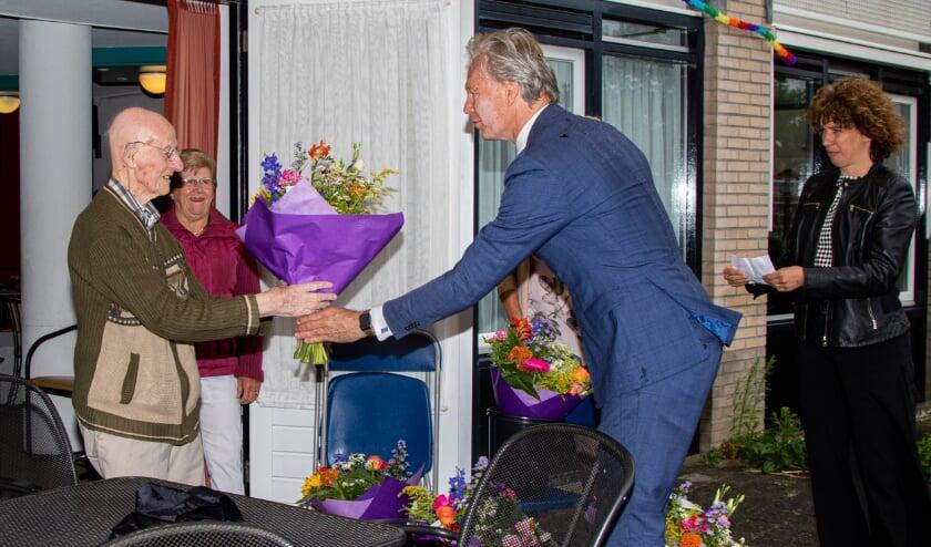 Wethouder Jeroen Joon overhandigt een bloemetje aan een jubilaris