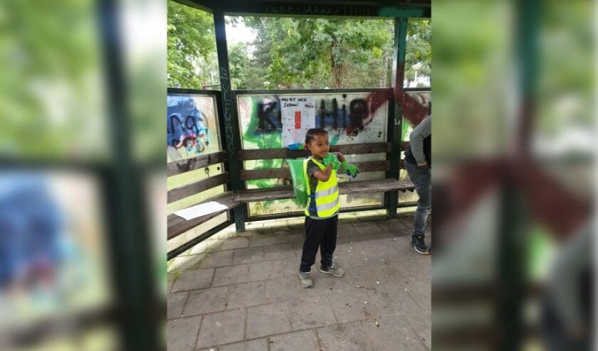 Jahlion (8 jaar) maakt samen met andere kinderen en studenten de bushokjes in de wijk schoon en roept buurtbewoners op het schoon te houden.