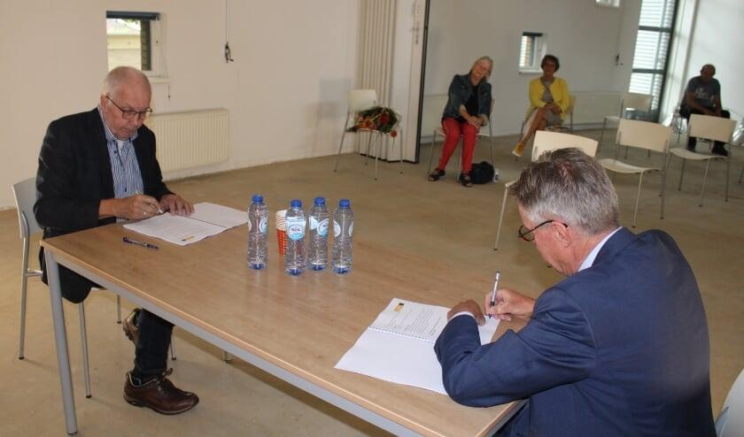 Jan Langhenkel (l) en wethouder Jan Berkhoff ondertekenen het contract terwijl mevrouw Langhenkel al een boeket heeft ontvangen.