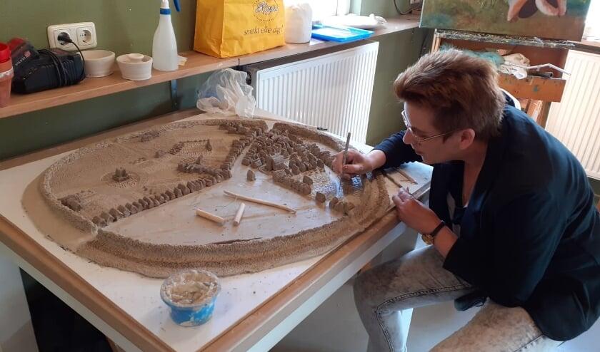 Kunstenares Ingrid Hegeman is volop bezig met de maquette van  Rijssen in de middeleeuwen. De stadswallen zijn duidelijk te zien evenals de Schildkerk en links kasteel Bevervoorde.