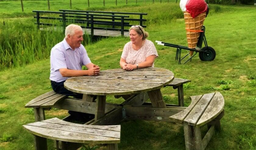Het echtpaar Van Zijtveld aan een van hun ronde picknicktafels op hun erf met de kenmerkende plastieke ijshoorn op de achtergrond.