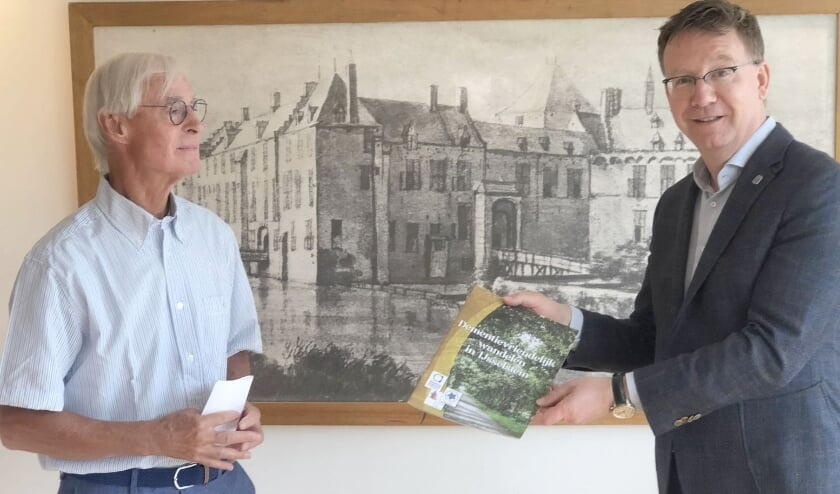 Fred Haas van de Werkgroep Dementievriendelijk IJsselstein overhandigde burgemeester Van Domburg het eerste exemplaar van de brochure Dementievriendelijk wandelen door IJsselstein. (Foto: Bernard Brosi)