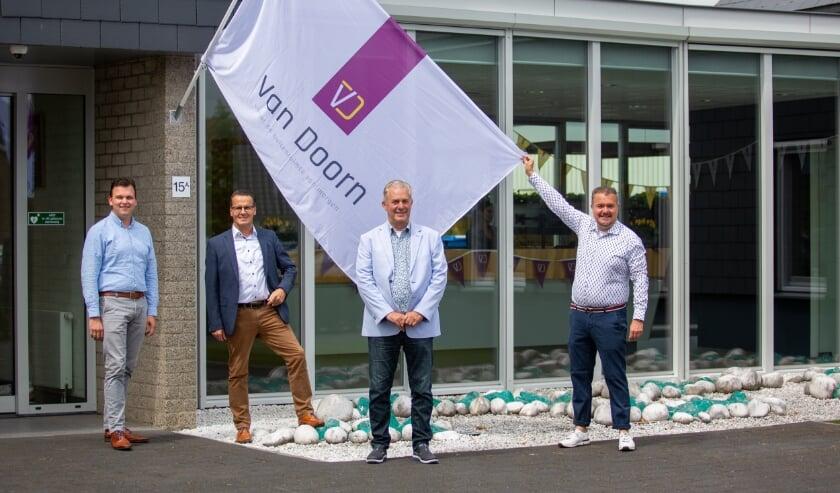 De directie van Van Doorn hijst samen de nieuwe vlag