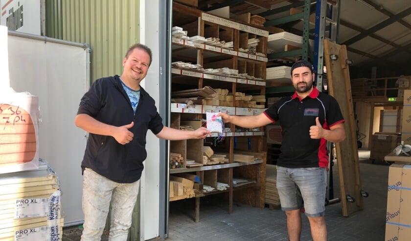 Berry Schut (links) overhandigt de bon aan 'bouwambassadeur' Yusuf Terlemez.