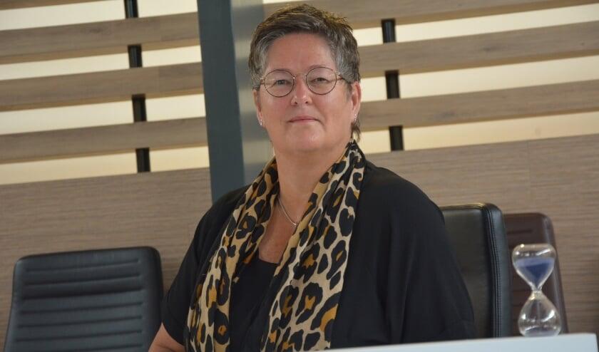 Plaatsvervangend voorzitter van de Elburgse gemeenteraad Liesbeth ten Have op de stoel van de voorzitter. met voor zich de zandloper.
