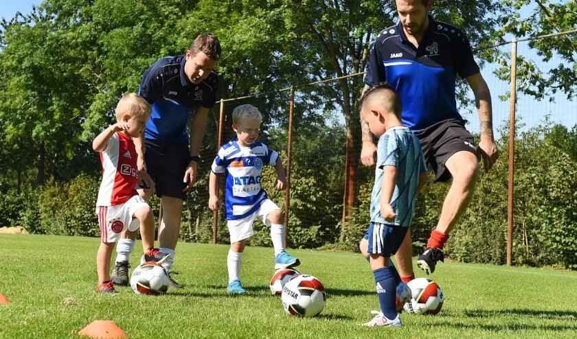 Pieter Paul Melissen (tweede van links) en Frank Pol (rechts) leren Lucas, Gavin en Alistair spelenderwijs voetballen. (Foto: Roel Kleinpenning)