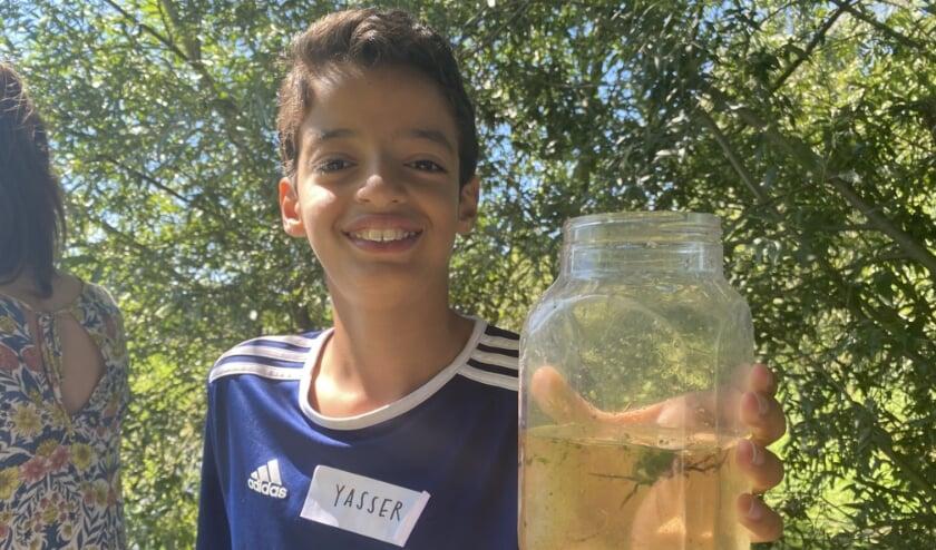 Yasser toont trots het door hem gevangen slootdier