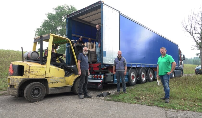 <p>Het transport wordt geladen door vrijwilligers. Op de voorgrond: chauffeur Jaap van der Spek, Peter Eckhardt en chauffeur Ron Heikoop.</p>