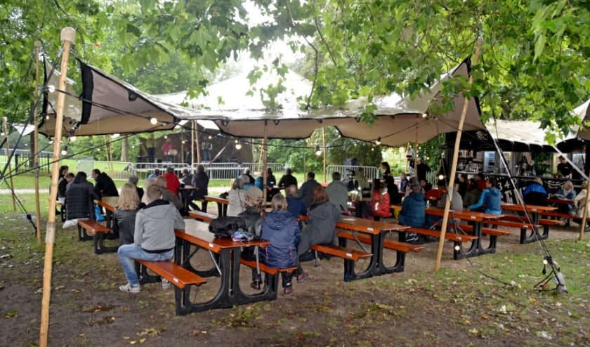 <p>Op het podium speelt Folkcorn. De regen van zondagmiddag maakte het knus en gezellig in de tent in het Torckpark (foto Jan Boer)</p>