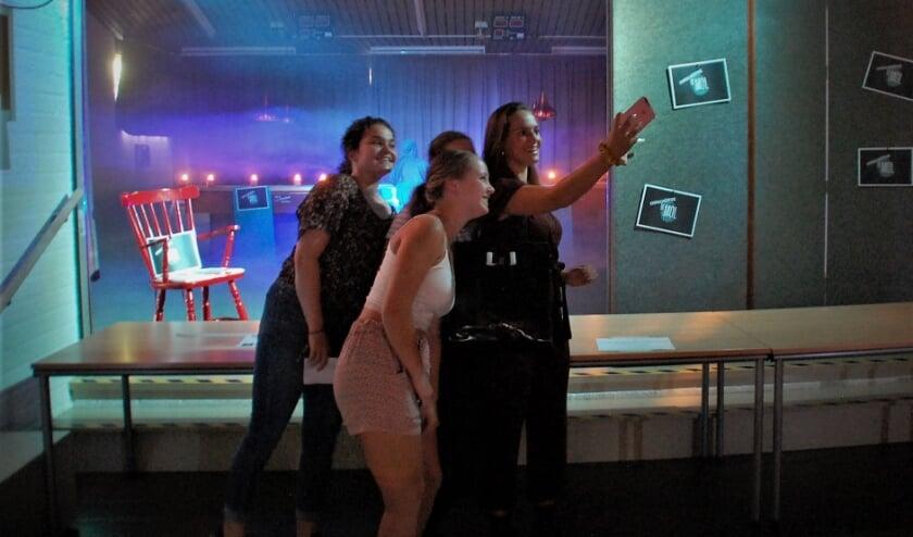 De meiden van groep Volle G maken een selfie met op de achtergrond De Mol, nog net zichtbaar in zijn/haar mysterieuze blauwe monnikspij.