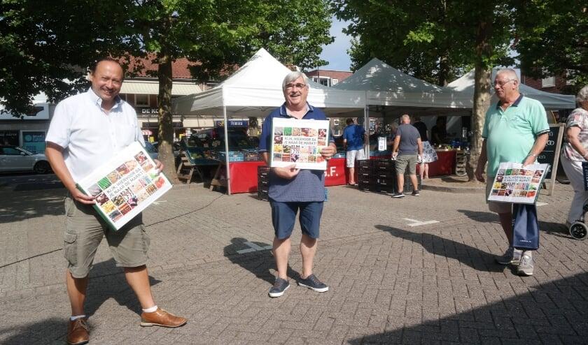 Drie personen ontvangen een tas op de markt in zuid.