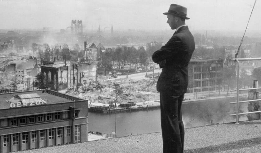 Verzetsstrijder Frits Nieuwenhuijsen kijkt vanaf het dak van het Erasmusgebouw uit over de stad na het bombardement in mei 1940.