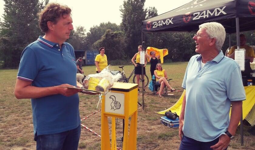 Kinderdorpvoorzitter Wim Spier biedt burgemeester René Verhulst een lunchpakket aan, broodjes met Kinderdorp Knaks!