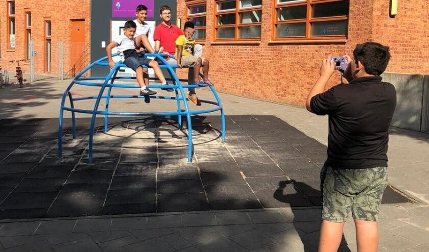 Kinderen leren foto's maken op de Zomerschool.