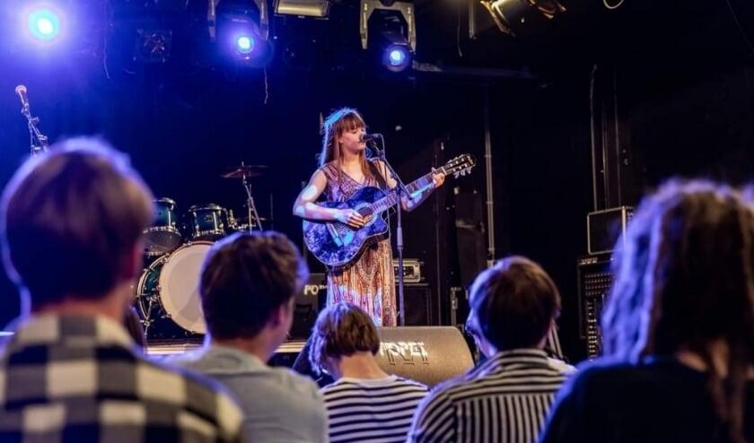Kyra Antoni optredend met gitaar.