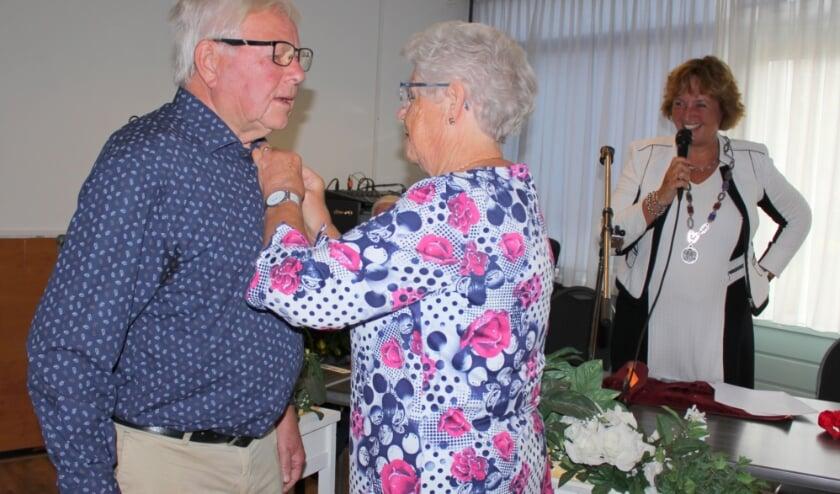 <p>Margo Pos spelt het lintje op bij man Marcus. &quot;Als u geprikt wordt, heb ik het niet gedaan&quot;, grapt burgemeester Spies. FOTO: Morvenna Goudkade </p>
