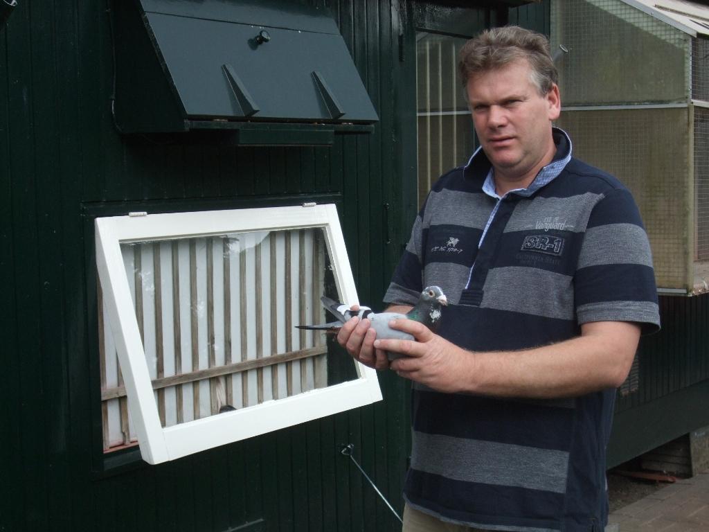 Jan Karsten met de prijswinnende duif.  Foto: Luchtvermaak Wierden  © DPG Media