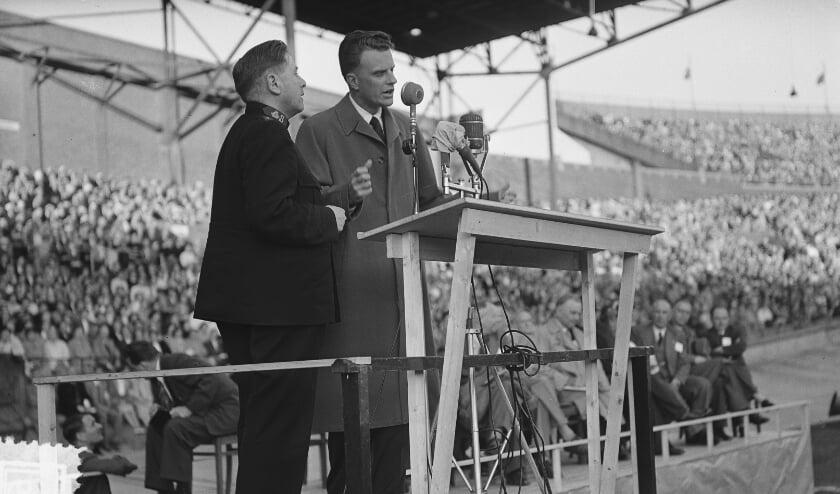 De Amerikaanse evangelist Billy Graham spreekt op een bijeenkomst in het Olympisch Stadion in Amsterdam, juni 1954. Fotograaf: Joop van Bilsen / Nationaal Archief