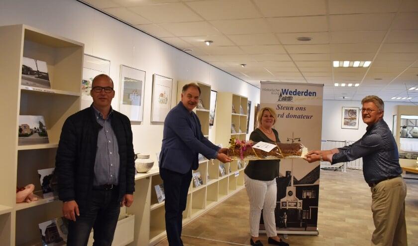 Vice-voorzitter Theo Pigge ontvangt van Bram Egberts en Jantine Langenhof de krentenwegge. Helemaal links Albert Hakvoort. (Foto: Van Gaalen Media)