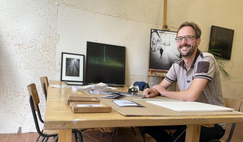 Peter van der Werf zoekt in zijn atelier bij R10 foto's uit voor Open Ateliers 2020