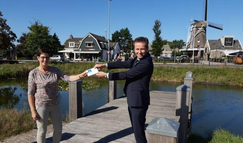 <p>wethouder Arjan Klein overhandigde aan Toos Bos een VVV-bon.</p>
