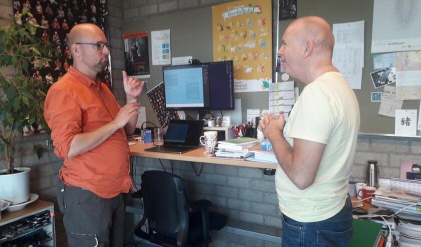 <p>Onno Crasborn (links) ondersteunt zijn spraak met gebaren voor collega-onderzoeker Tom Uittenbogert&nbsp;</p>