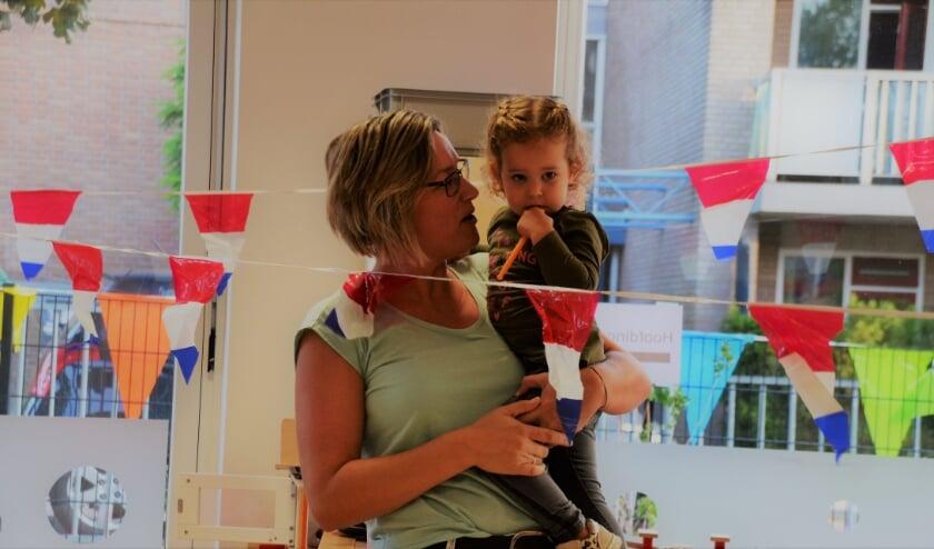 <p>Pedagogisch medewerker Vera met Tess met op de achtergrond de feestelijke versieringen. (foto: Riet Sloot)</p>