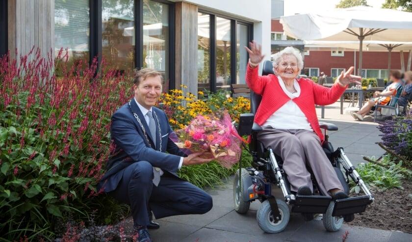 <p>Burgemeester Kats overhandigt een bloemetje aan de 100-jarige mevrouw Ebbers in zorgcentrum De Meent.</p>