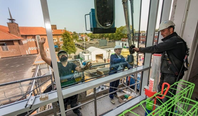 Wethouder Marcel Melissen van de gemeente Tiel plaatst onder deskundige begeleiding één van de eerste ramen in het nieuwe gebouw van het Lingecollege lyceum.