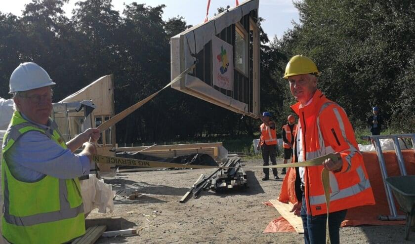 <p>Wethouder Bart de Leede(links) takelt met een ijzige precisie het bouwelement op het gebouw van de scoutingclub Maurits-Vioolgroep en daarmee was meteen ook het hoogste punt bereikt. Foto: Peter Spek</p>