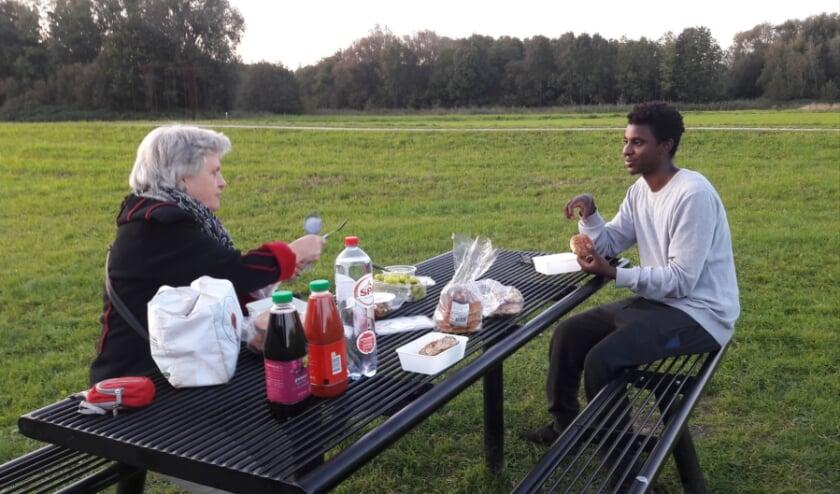 <p>Els Wallenburg met de Ethiopische student Ammanuel Bekele genieten van een corona-proof lunch tijdens een fietstocht door de omgeving.&nbsp;</p>
